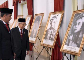 Presiden Jokowi bersama Wakil Presiden Ma'ruf Amin melihat foto Rohana Kuddus usai penganugerahan gelar pahlawan nasional. (Setpres/Biro Pers)