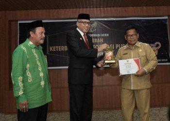 Plt Gubernur Aceh menyerahkan piagam penghargaan anugerah. (Humas dan Protokoler Setda Aceh)